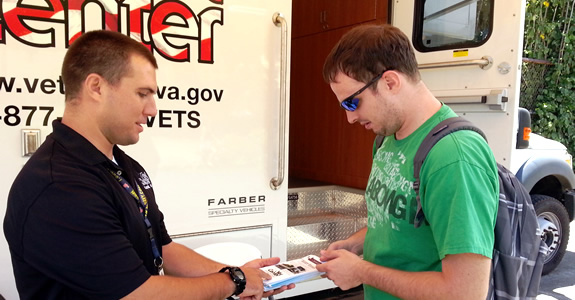 VA worker Travis Schmidt providing information to a UH student - Mobile Veterans Center, Fall 2013.